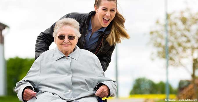 junge Frau schiebt Rollstuhl alter Frau