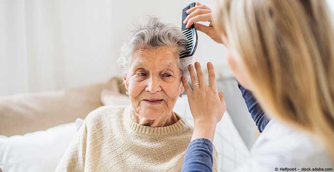 junge Frau frisiert Seniorin