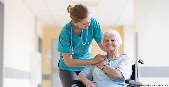 junge Pflegerin mit Seniorin in Rollstuhl