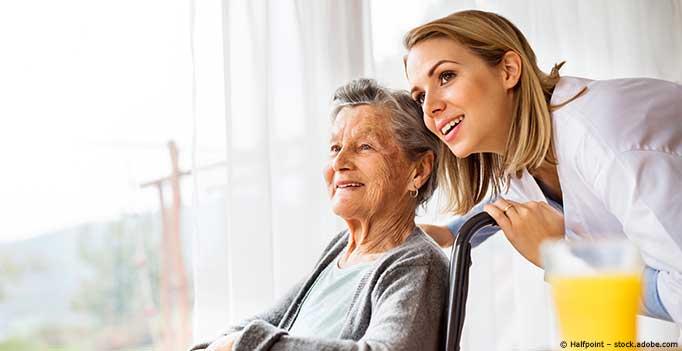 Pflegerin mit Seniorin in Rollstuhl