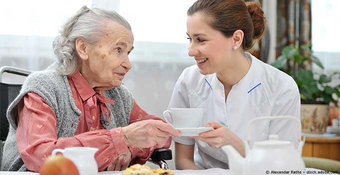 Pflegerin und Seniorin am Kaffeetisch