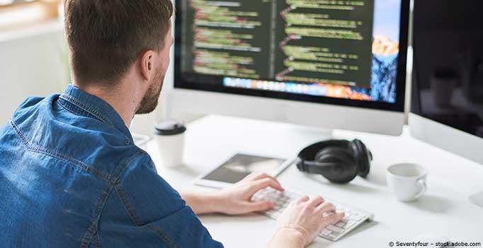 Mann schreibt Code am Computer