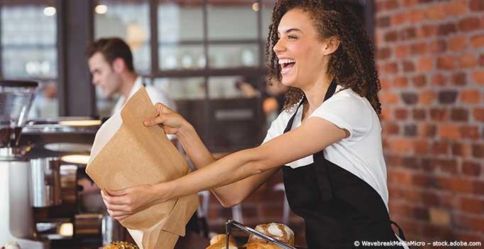 lachende Frau verkauft Backwaren